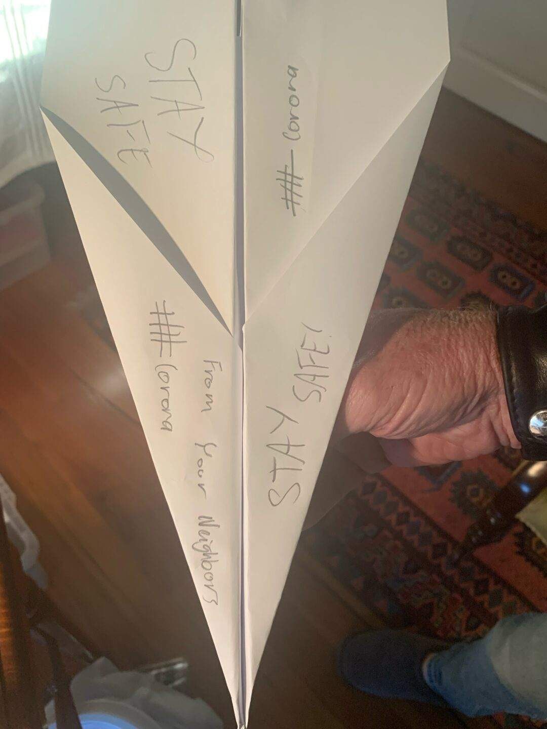 One white paper airplane with 'stay safe' and #Corona written on it in pencil. It is being held my a hand, and a polished wooden floorboard with a rug are visible.