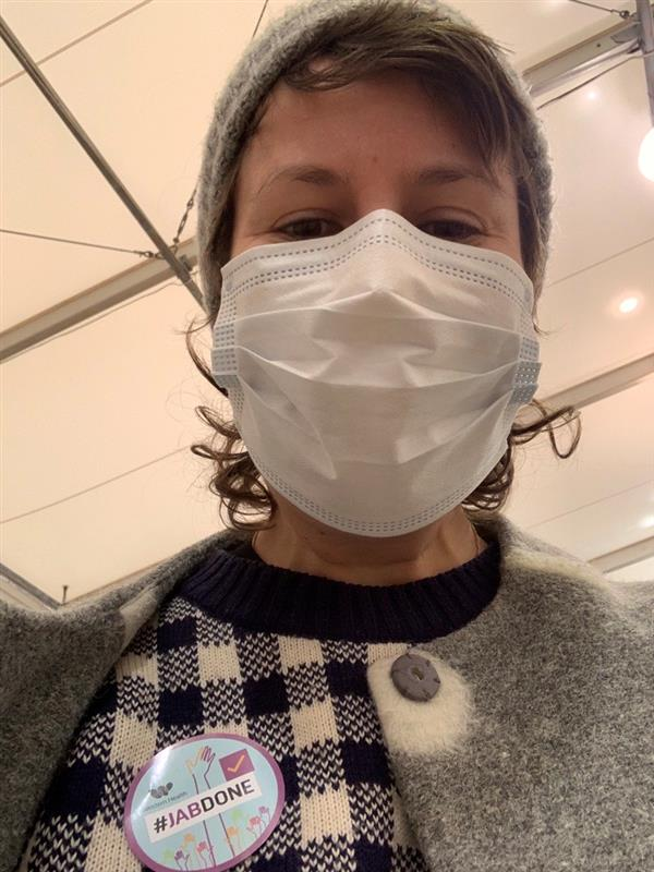 Selfie of a young woman ina grey beanie, black and white check jumper and a grey coat, wearing a surgical mask. She wears a blue circular sticker which reads #jabdone
