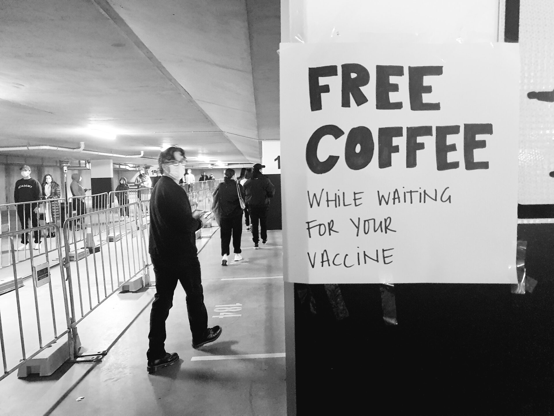 a hand written sign that says 'free coffee while waiting for your vaccine'