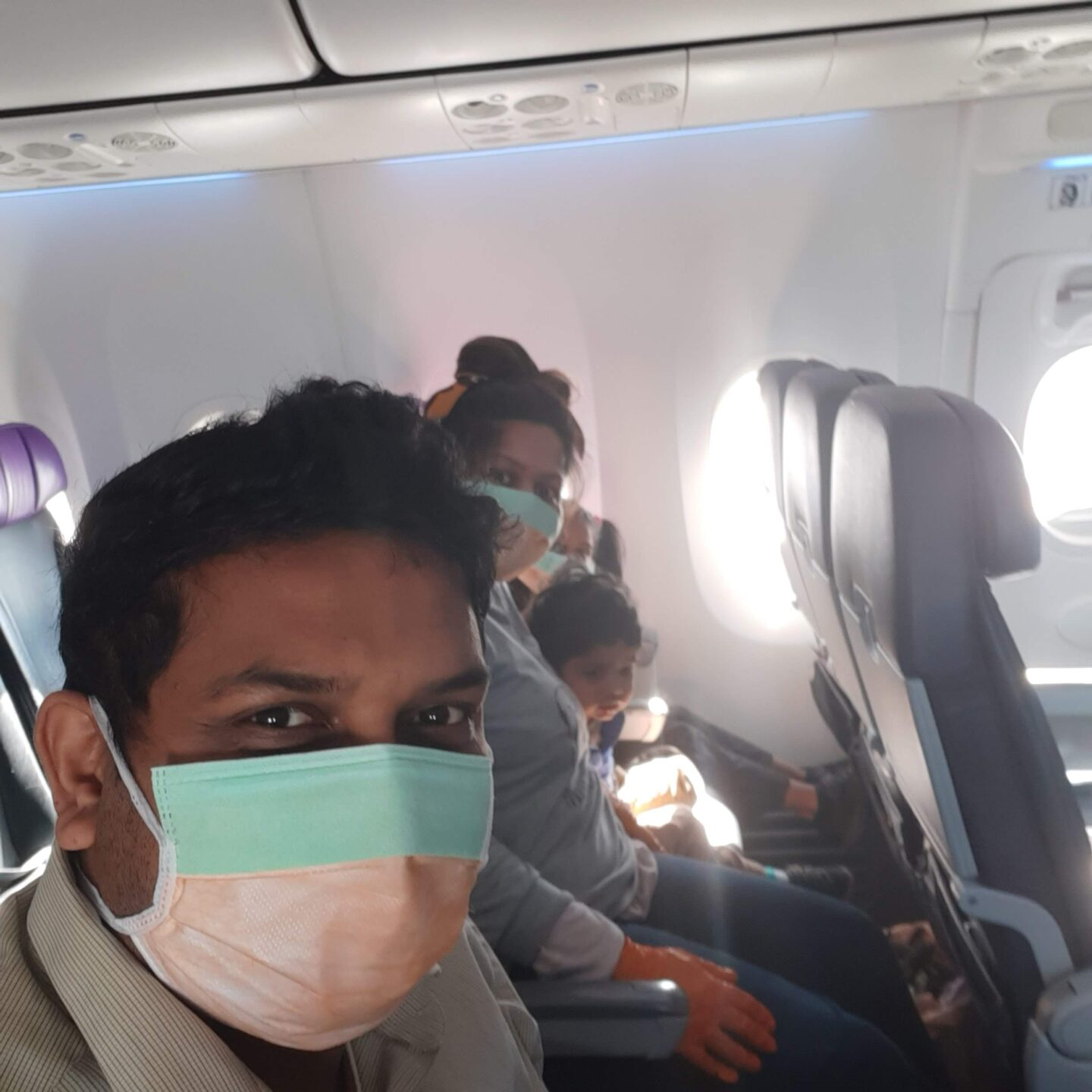 A man in a mask on an aeroplane with his family in the background also in masks.