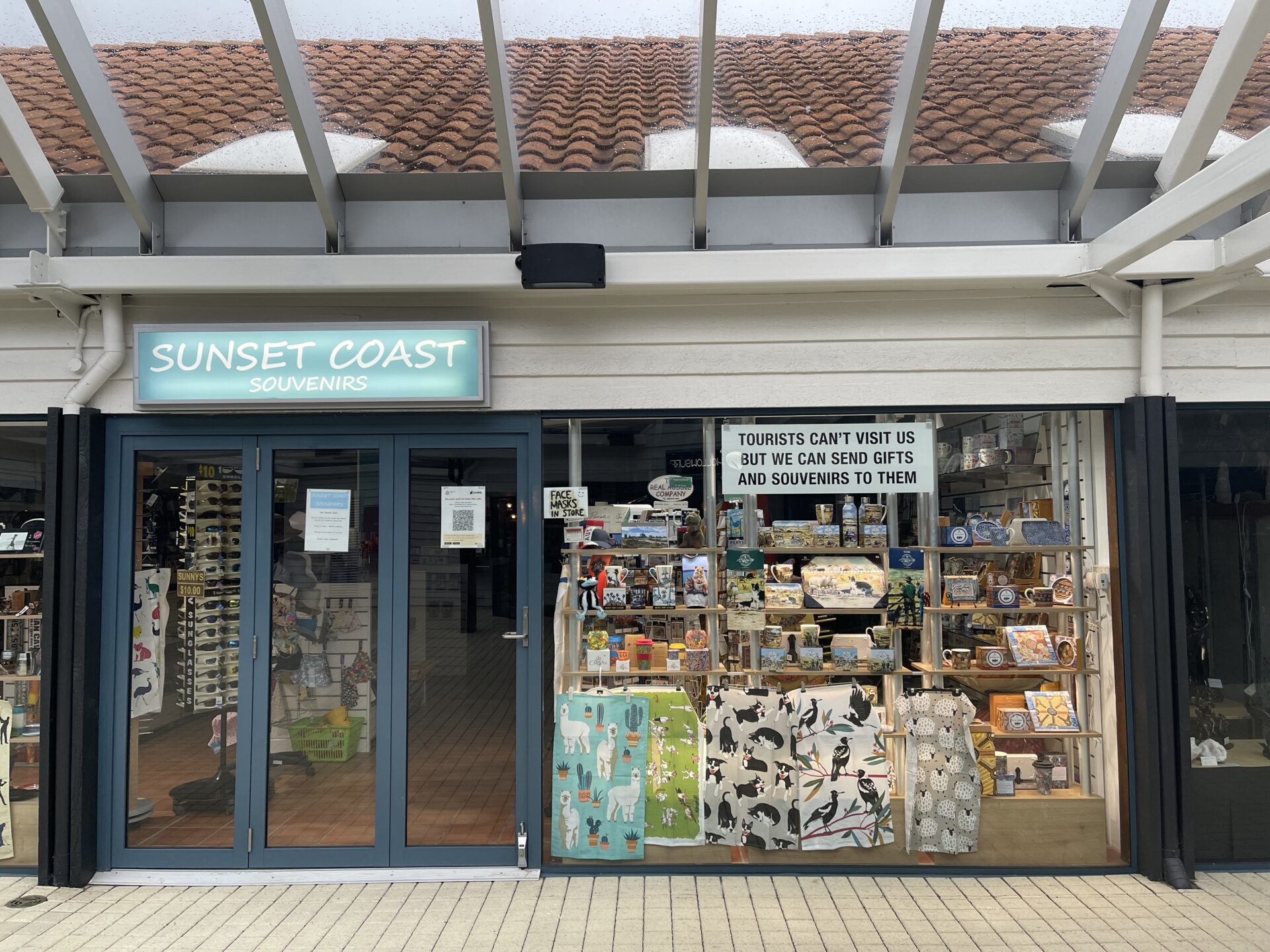 Front of a closed Australiana kitsch-souvenir shop, with an aquamarine sign reading 'Sunset coast'