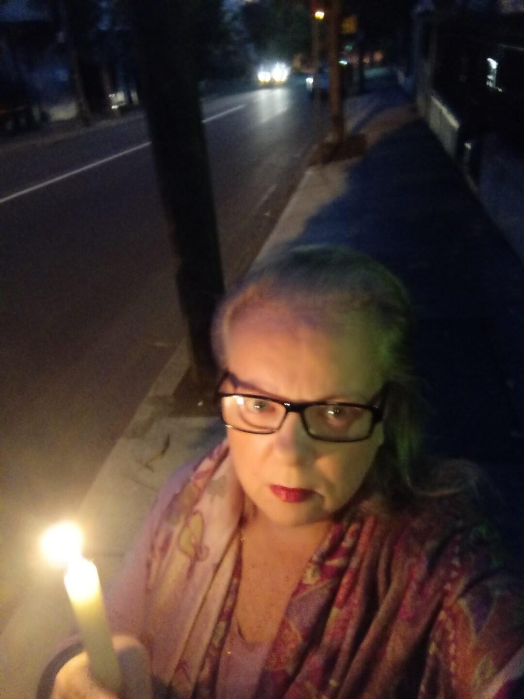 A woman holding a candle outside at dawn.