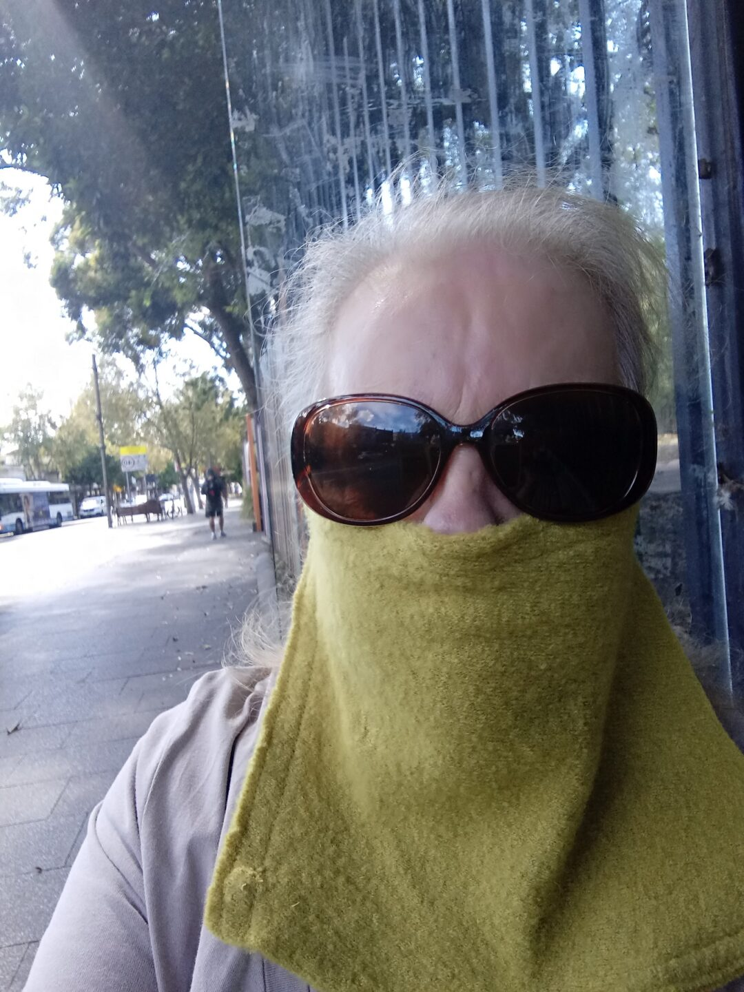 A woman with grey hair and sunglasses wearing a hand made mask.