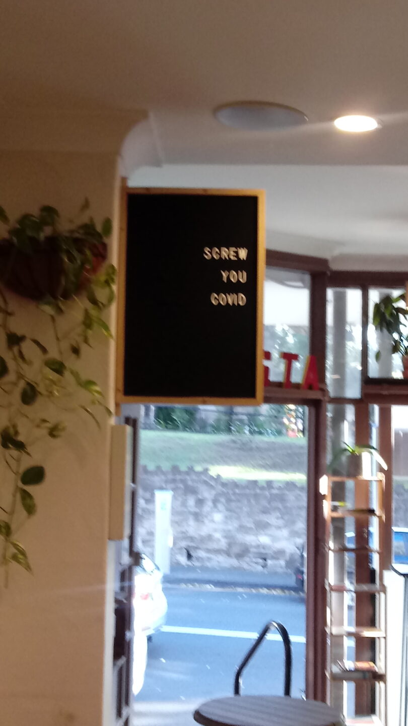 A sign in a cafe that says 'screw you covid'