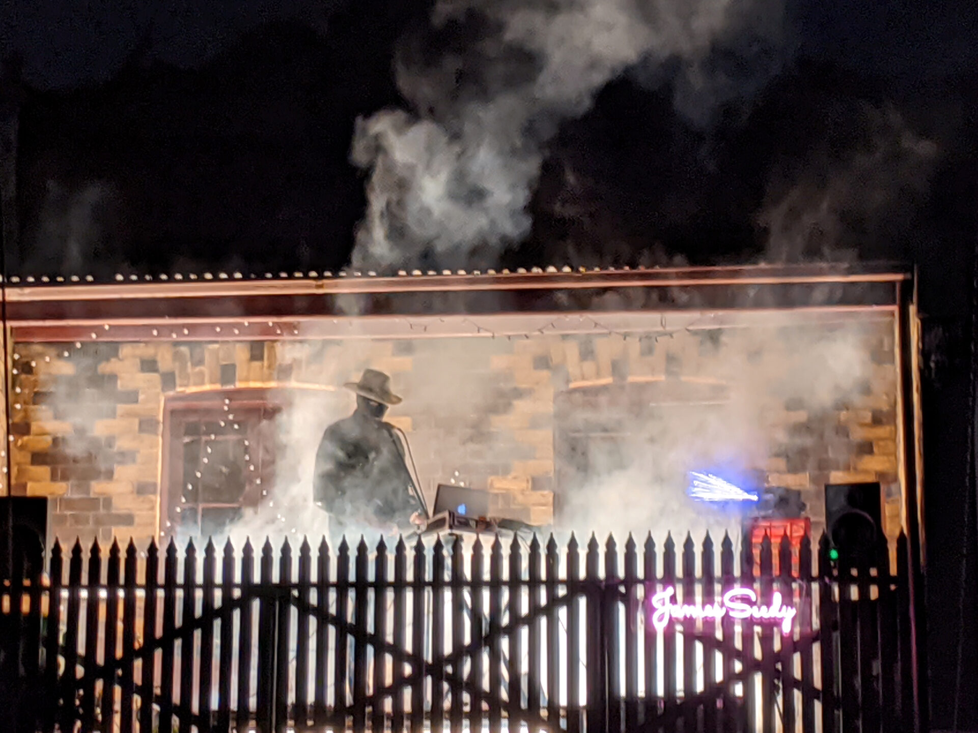 Nighttime. A brick building partially concealed by smoke, with a male hatted figure silhouetted. In the foreground is the profile of a picket fence.