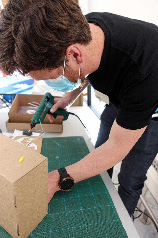 a man in a mask using a glue gun onto a brown shoe box.