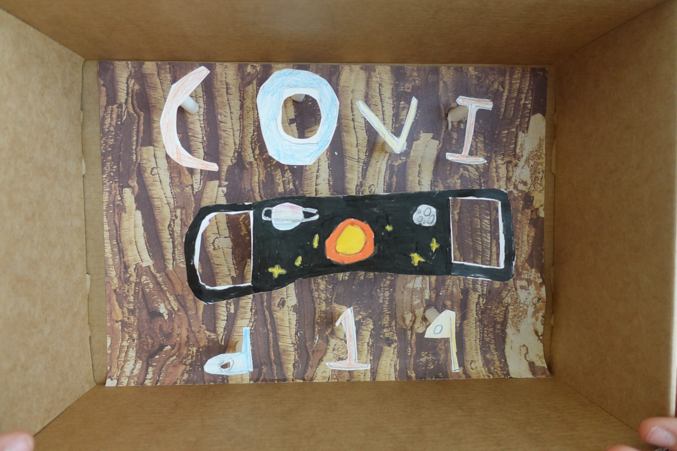a diaorama inside a show box with a mask made from paper and the words covid 19 around it.