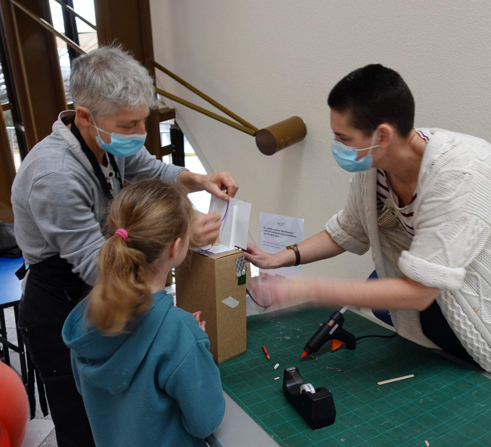 Two adults and one child gluing paper and other materials to a cardboard box