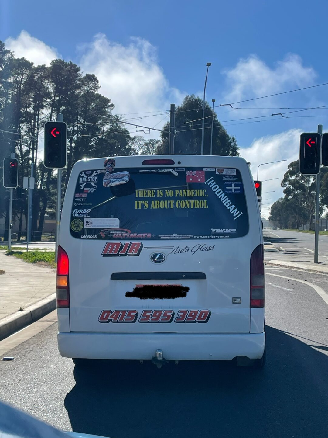 Rear of a white van stopped at lights in daytime. A vinyl sticker on the back window reads THERE IS NO PANDEMIC IT'S ALL ABOUT CONTROL. The window has a lot of other stickers.