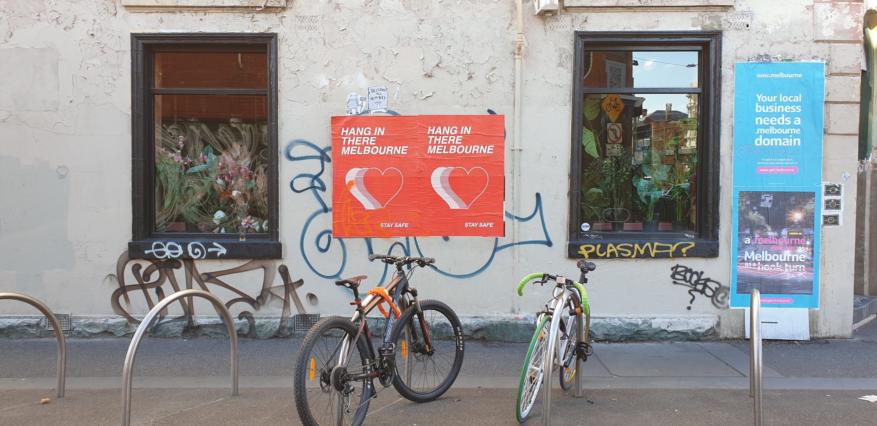 A photo of the side of a Melbourne building with two red posters on it. four bike racks and two bikes are in the foreground.