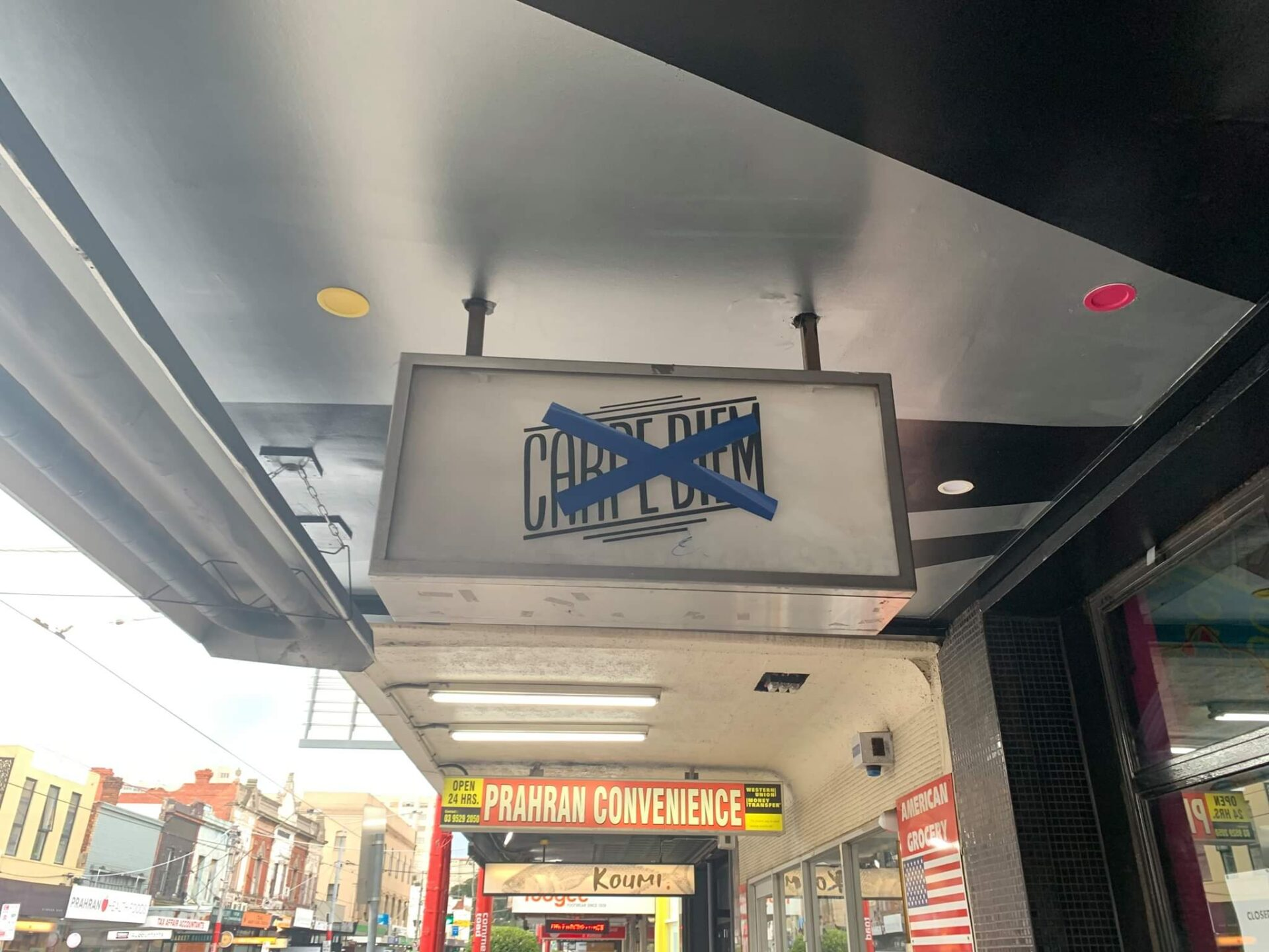 A light box sign bolted to a shop veranda with blue tape crossing out the name of the venue.