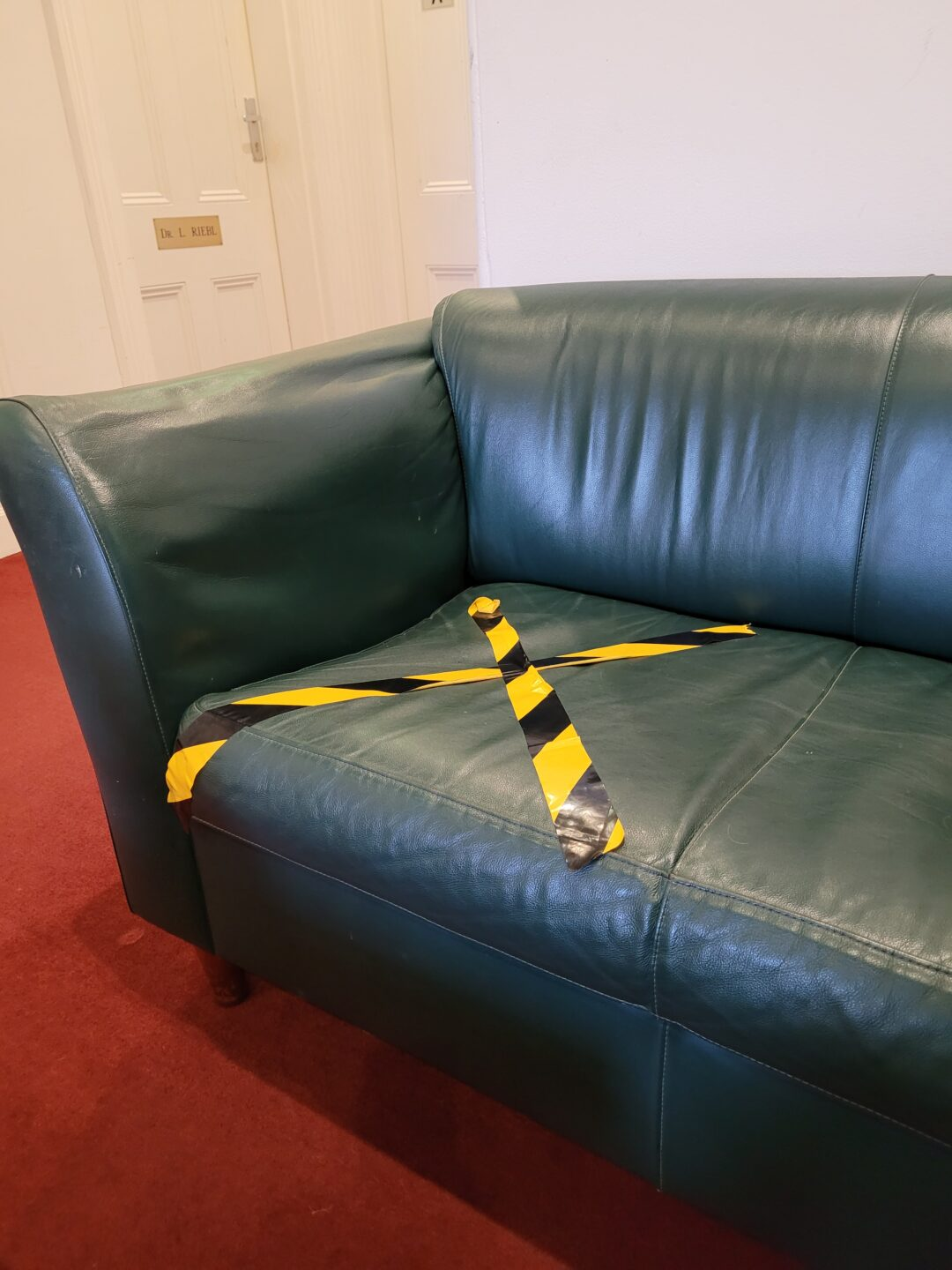 A forest green couch with black and yellow tape in the shape of an X to mark where a visitor can not sit.
