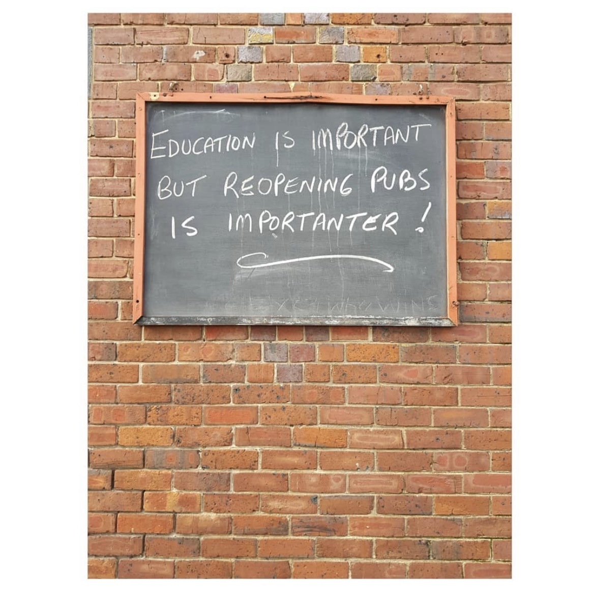 Black chalkboard hanging on a brick wall. White chalk lettering reads EDUCATION IS IMPORTANT BUT REOPENING PUBS IS IMPORTANTER!