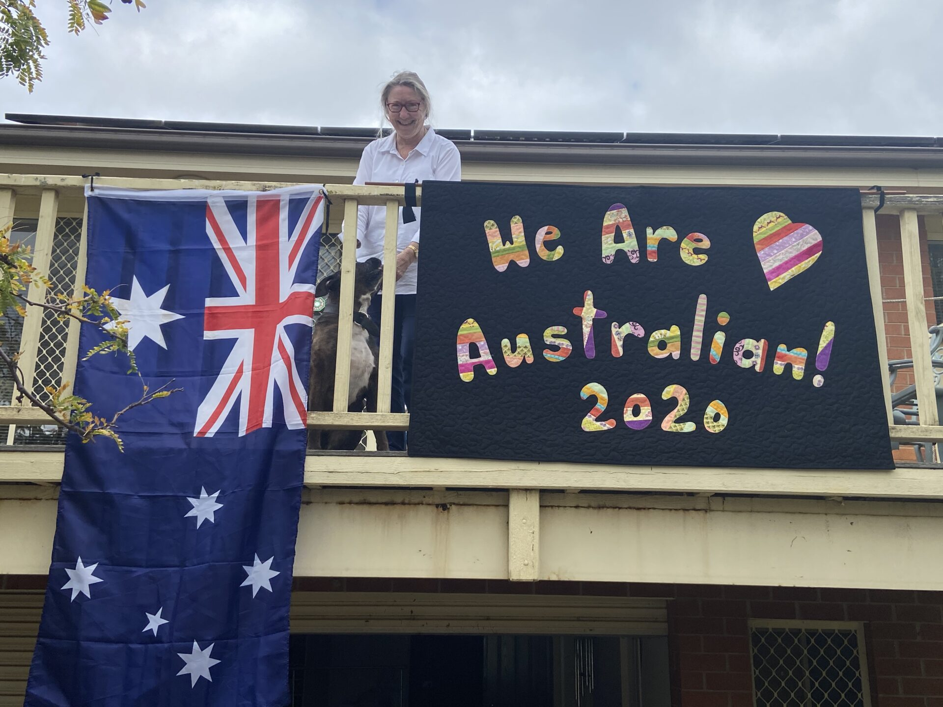 a handmade quilt with the words 'we are Australian 2020' suspended on a veranda next to an australian flag. In between the flag and the quilt is a woman wearing a white shirt and glasses.