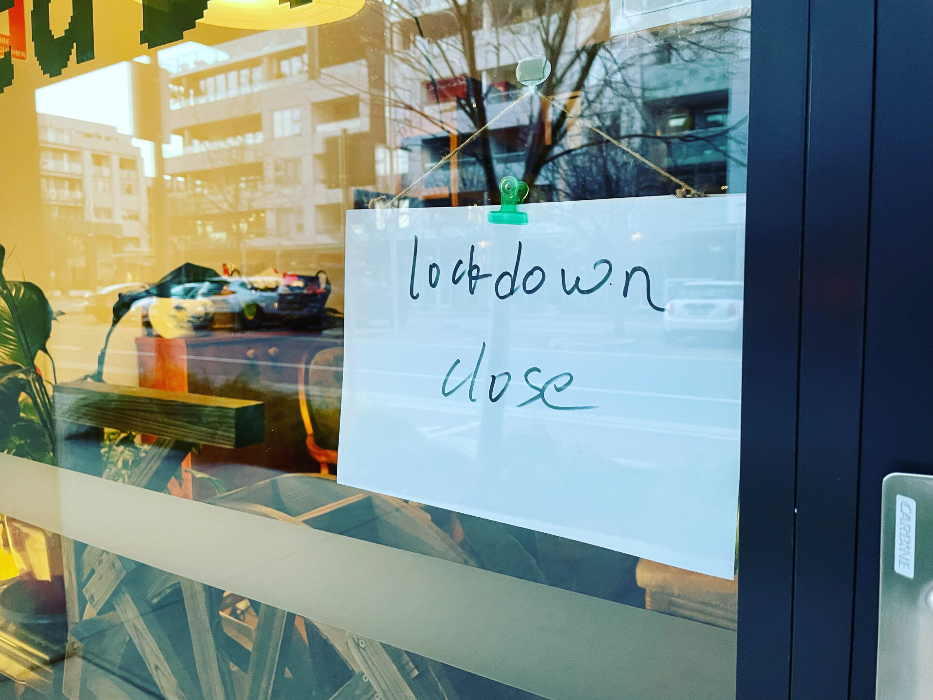 a hand written sign on an a4 piece of paper that says 'lockdown close' stuck to the door of a local business.