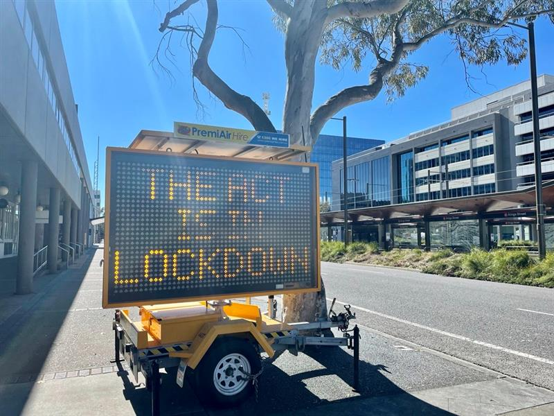 An empty city street in the daytime with an electric sign reading 'THE ACT IS IN LOCKDOWN'