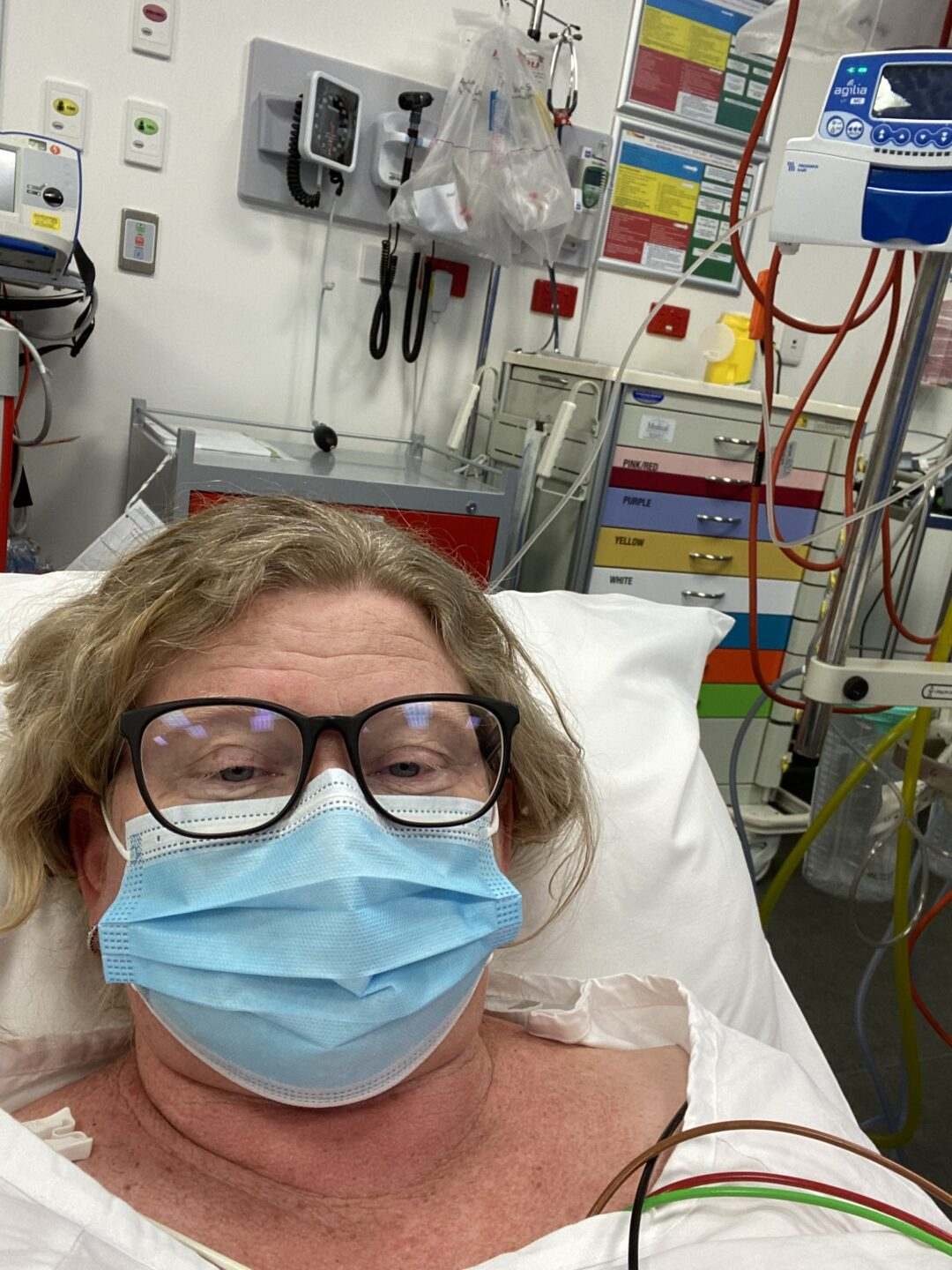 A women with blonde hair and glasses in a medical mask in a hospital bed