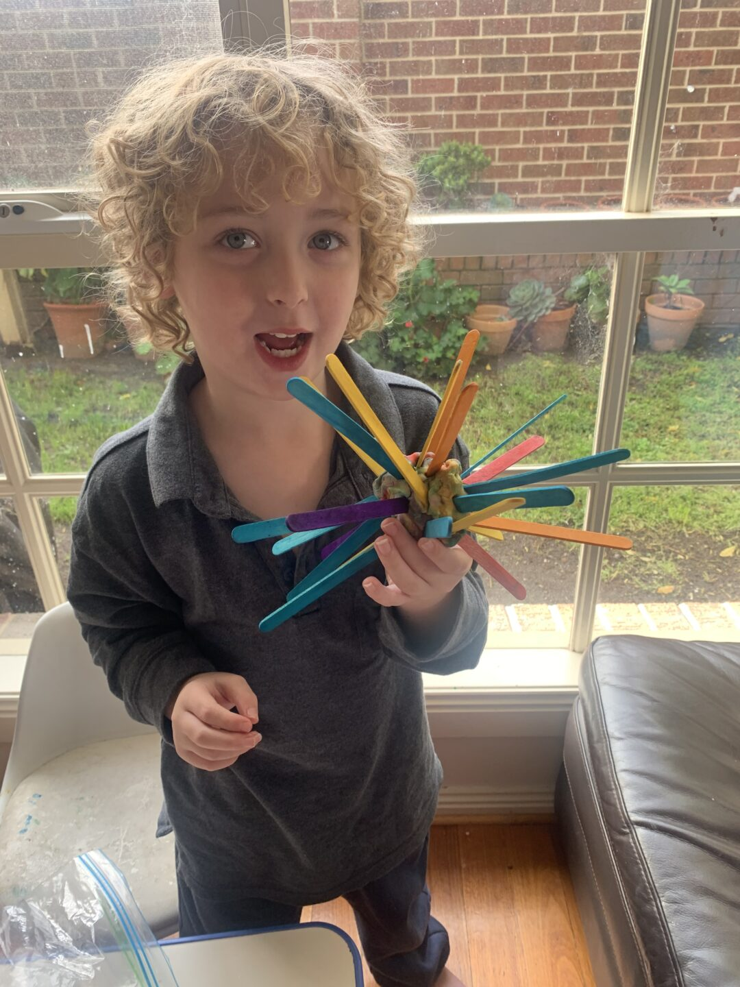 a young boy with curly blond hair holding a sculpture of a coronavirus spore made from pop sticks.