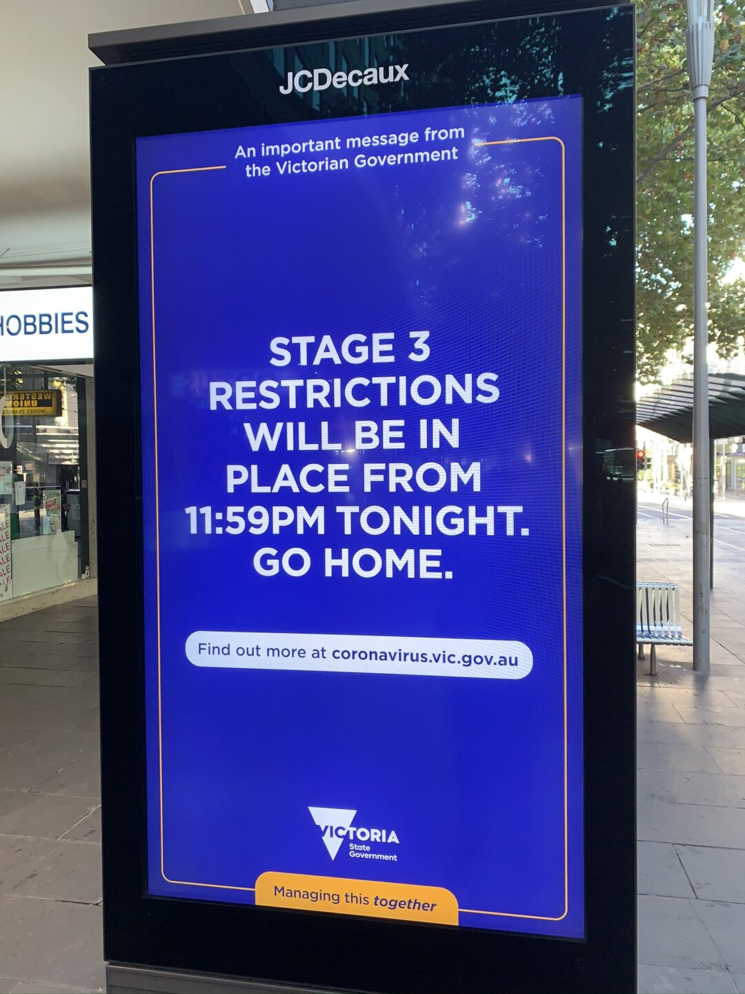 a bus stop sign that says 'stage 3 restrictions will in be in place from 11:59pm tonight. Go Home.'