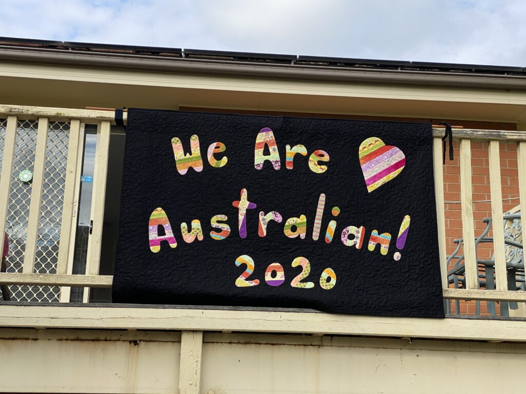 a handmade quilt with the words 'we are Australian 2020' stitched on it. The quilt is suspended from the side of a veranda balcony.