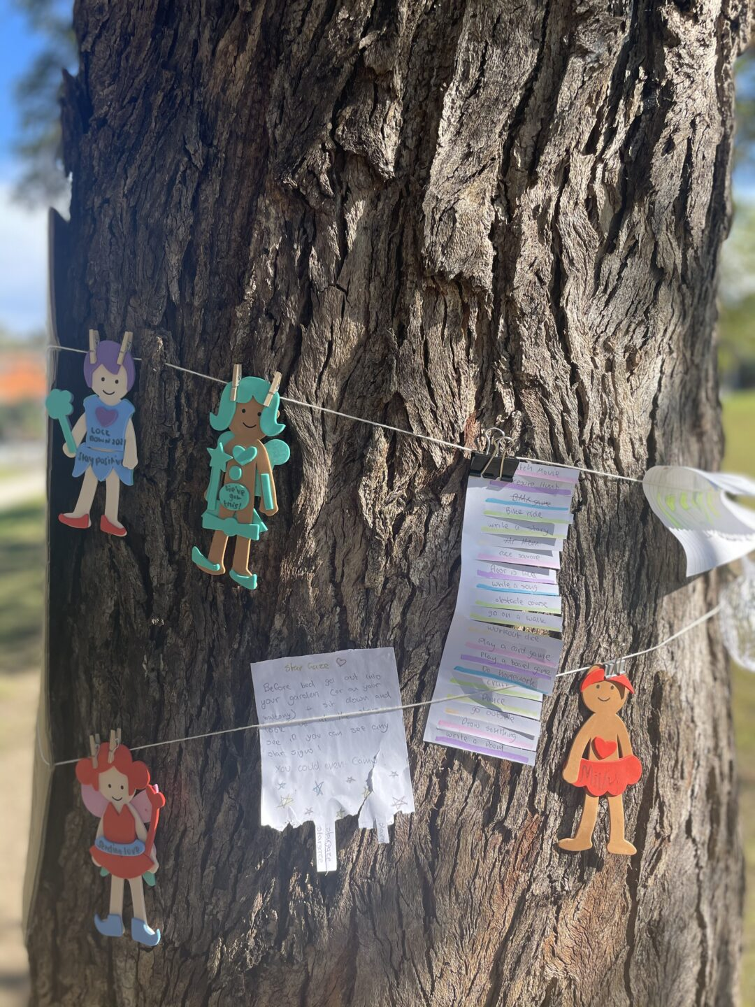Arts and crafts tied with string around a tree truck.