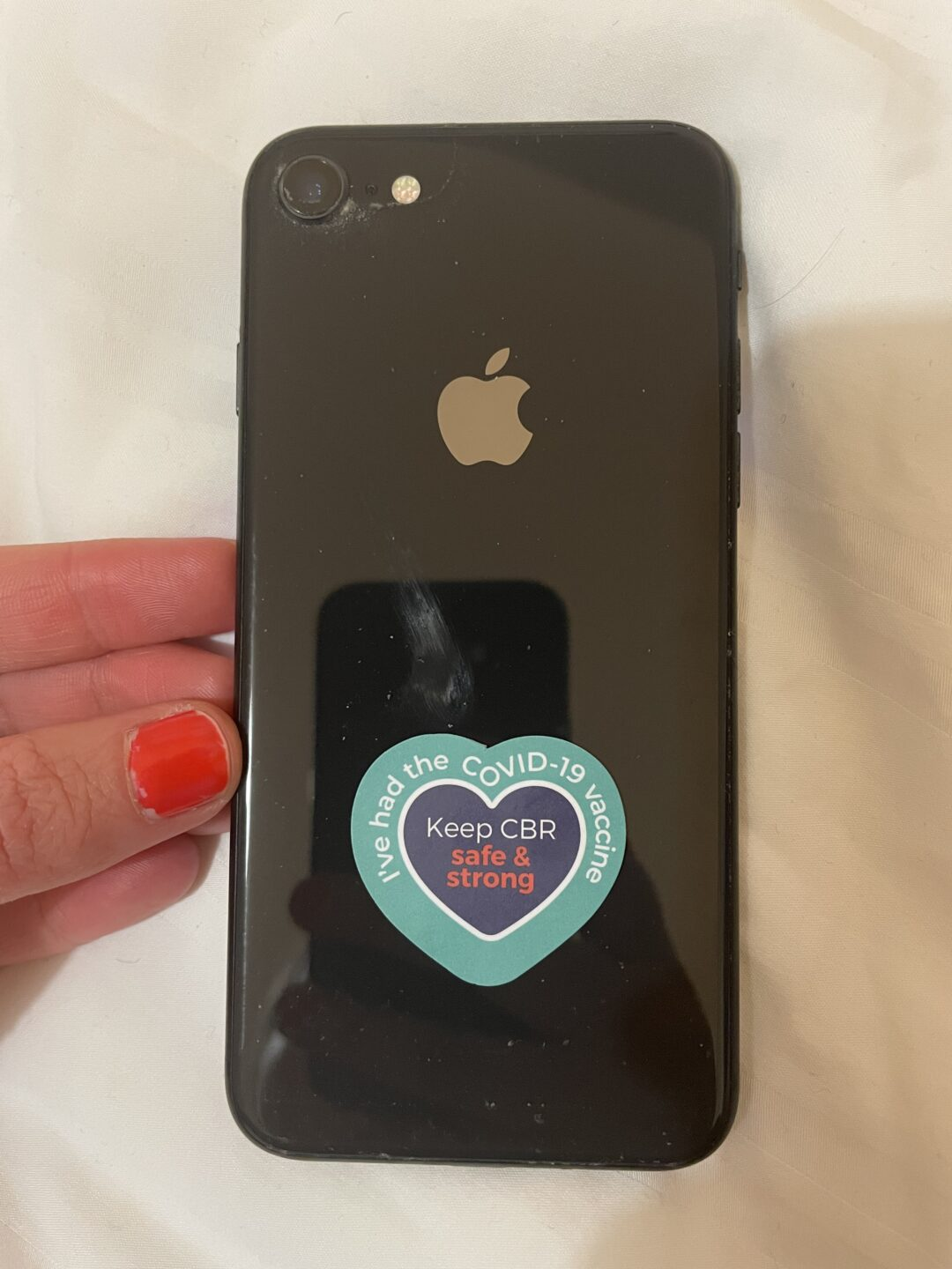Black apple phone with a blue and purple heart sticker at the bottom, reading 'I've had the COVID-19 vaccine / Keep CBR safe & strong'