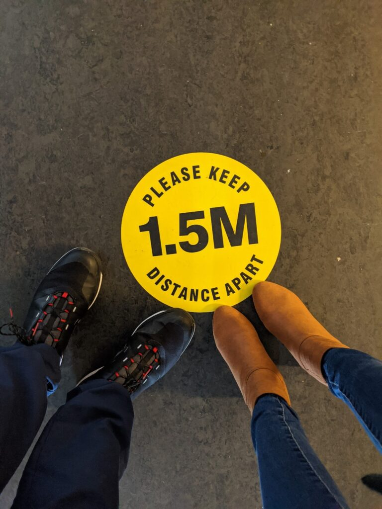 A yellow sticker on the ground telling people to keep 1.5 metres apart.