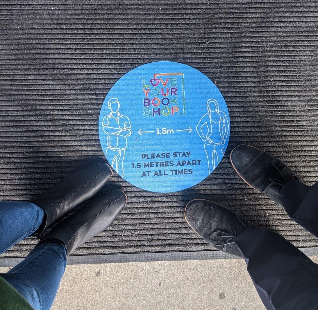 a blue sticker on the ground telling people to keep 1.5 metres apart.