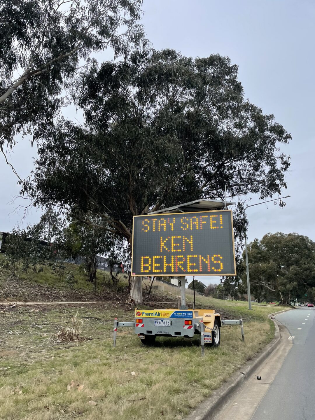 Overcast daytime scene. An electric sign by a road reading STAY SAFE KEN BEHRENS in orange illuminated lettering. Behind the sun is a large eucalyptus tree.