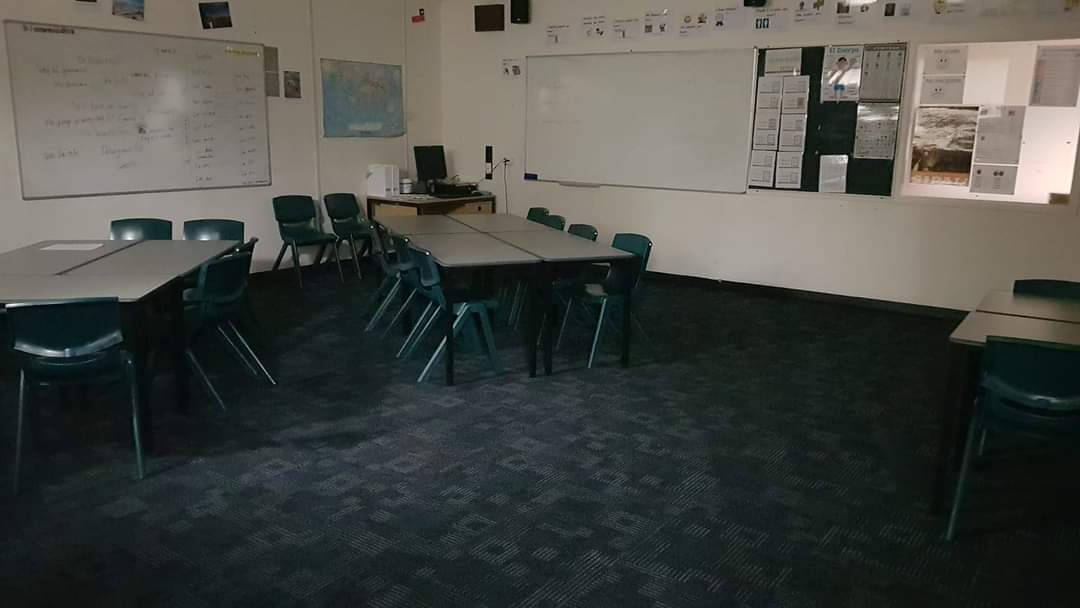 A classroom with white walls whiteboards with text written on it, and dark blue-grey carpet. Two rectangular tables with chairs are placed in the corner, and there are posters on the walls. The room is empty.