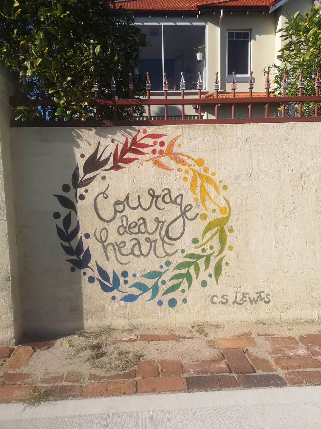 A daytime scene, with a concrete wall in front of a residential property. On the wall is stencilled in rainbow colours a wreath, with cursive text within reading 'Courage dear Heart' and an attribution to C.S. Lewis in the bottom right.