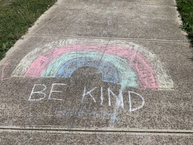 a chalk rainbow drawn on pavement with the words 'Be Kind' written underneath.