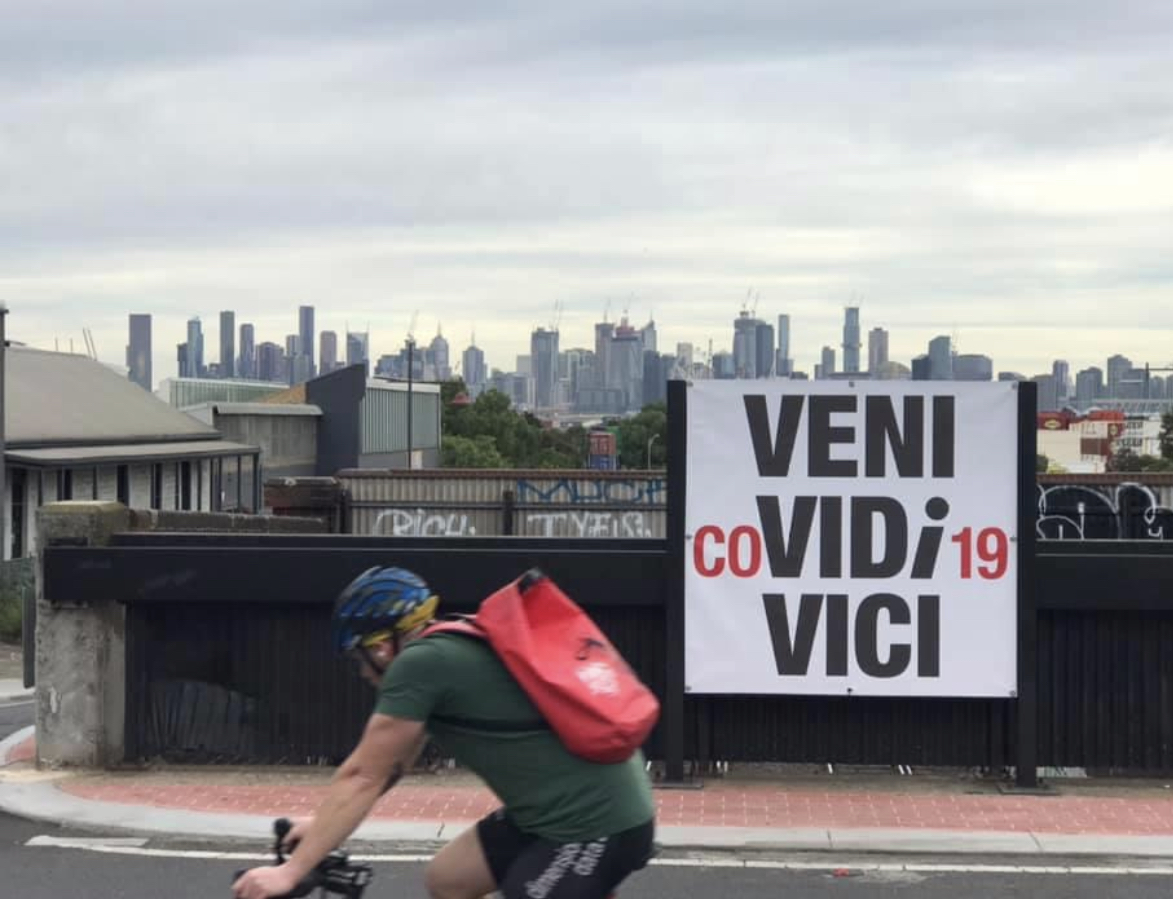 a view of the melbourne skyline behind a poster that says 'veni COvidi19 civi'. There is a bike rider in a green t shirt and red backpack in the forground.