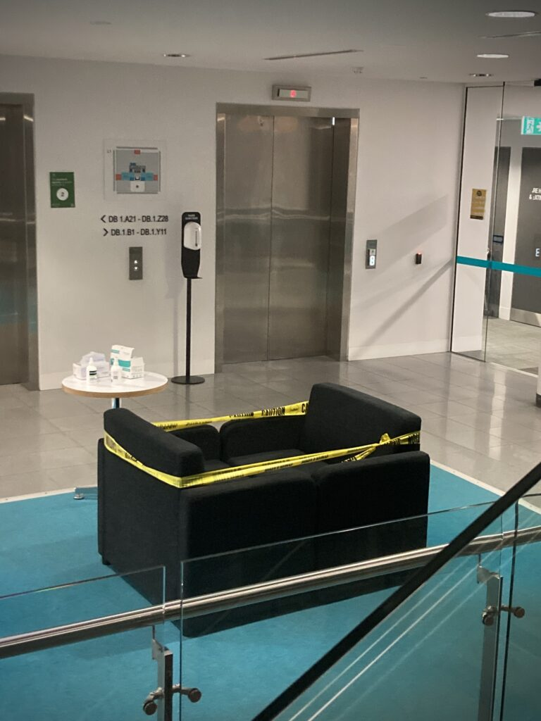 An image of seating in a pubic building wrapped with yellow caution tape.