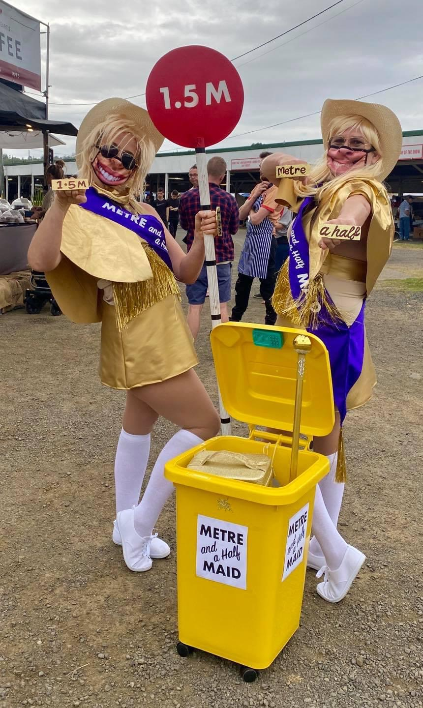 two women dressed in gold glitter outfits holding lollipop signs that say '1.5 m'