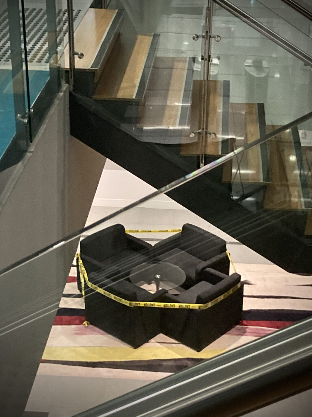 A photo of four seats in a public building wrapped with yellow caution tape.