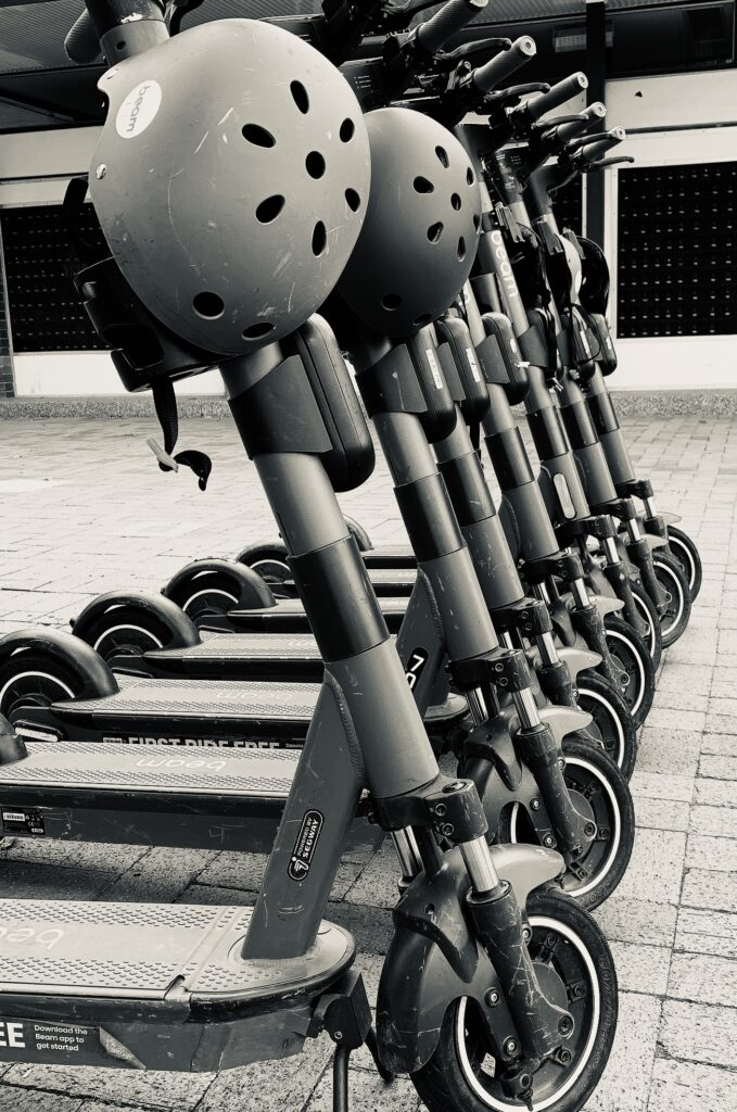 A black and white photos of e-scooters lined up.