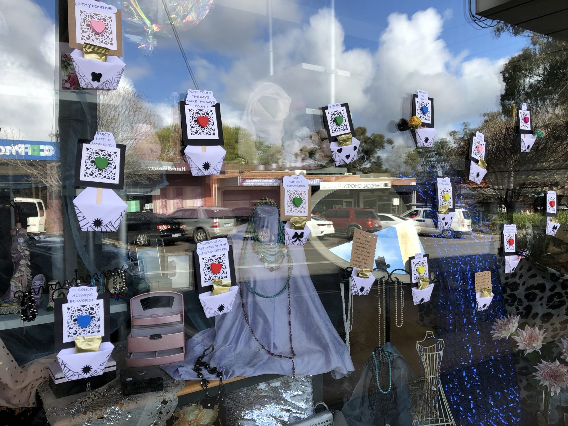 hand made pockets hanging from a shop window with sayings on them and free lollipops in them