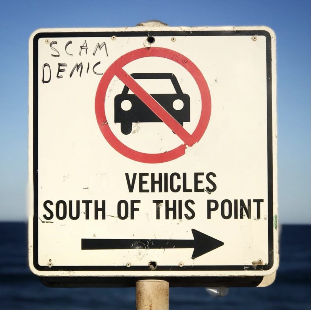 A photo of a street sign that indicated no parking of cars with the word 'scamdemic' graffiti-ed on it.