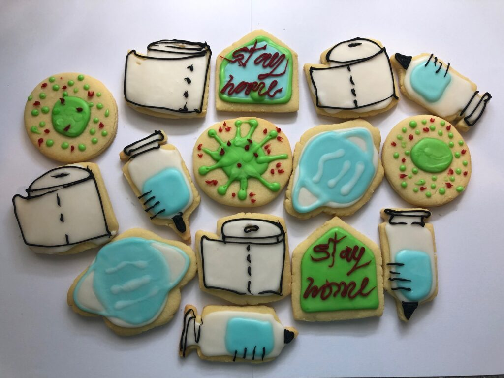 White background with 15 home-made biscuits with Covid-19 themed decoration with white, blue, green icing with red black and brown detailing. Toilet paper, the virus form, syringes and vaccine vials, as well as 'Stay Home' messaging.  - toilet
