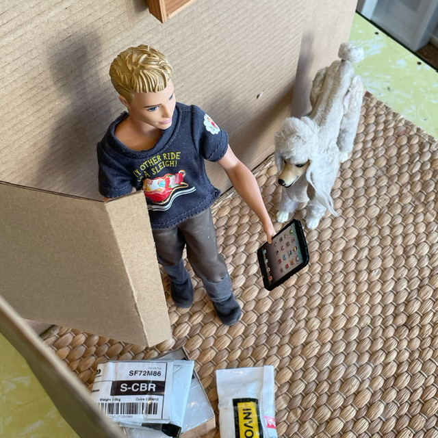 a male doll holding a phone and with a plastic toy poodle in a living room made of cardboard.