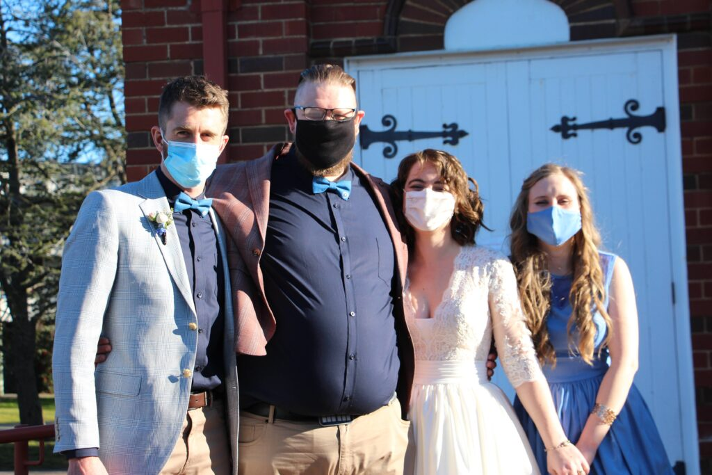 a bride and groom and two witnesses standing in front of a barn door.