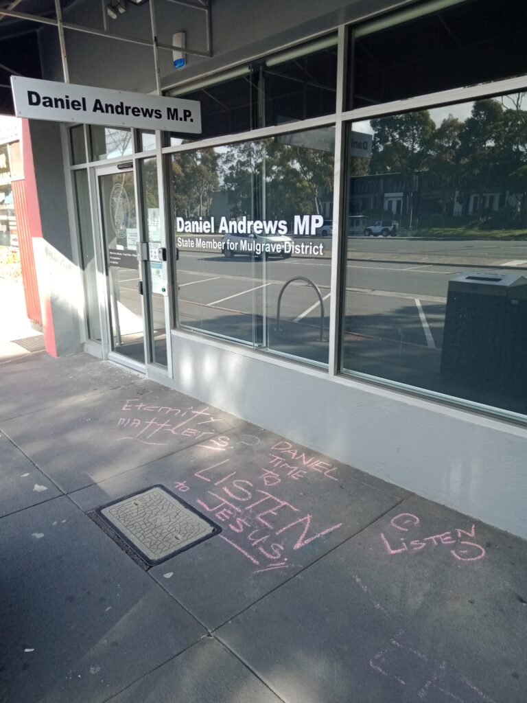 A photo of an office building with chalk drawings on the ground in pink chalk.