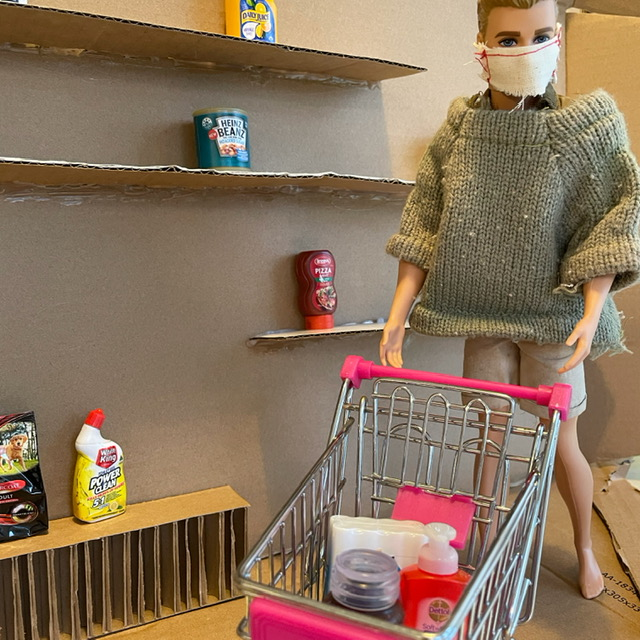a male doll in a mask pushing a plastic shopping trolley past a dolls house supermarket with empty shelves.