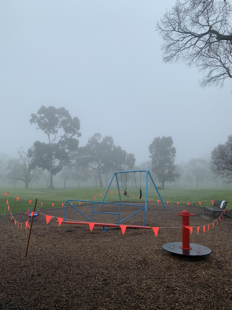 A frosty, foggy winter's morning. Blue children's play equipment is cordoned off by red and orange bunting.