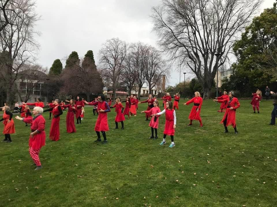 A group of dancers in a park wearing all red.